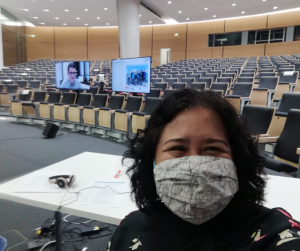 Conference Officer Diah wearing a face mask in an empty auditorium during a virtual event